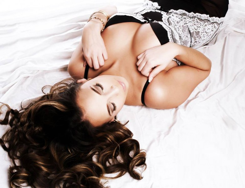 Glamour Shots Brunette woman in boudoir photo on bedsheets