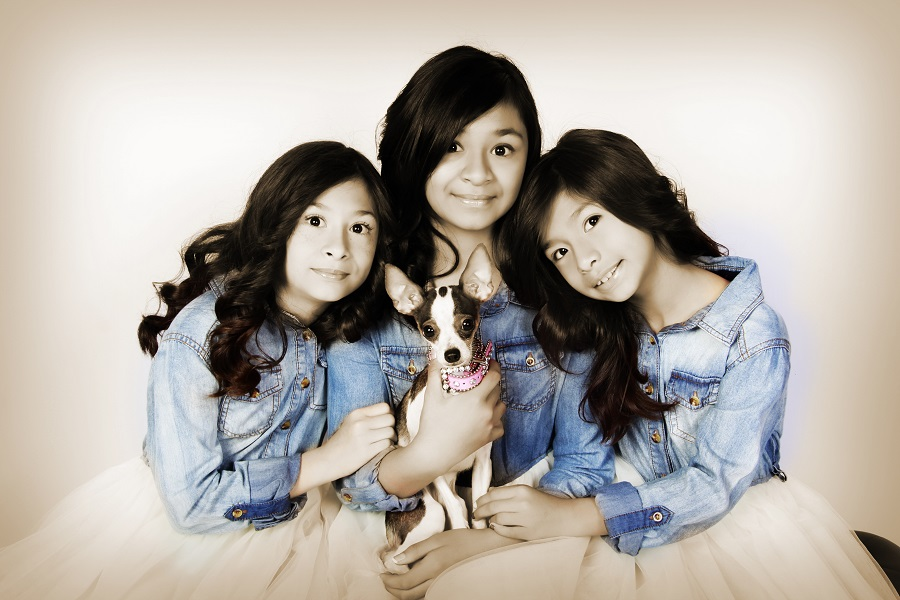 sisters wearing matching outfits holding Chihuahua dog